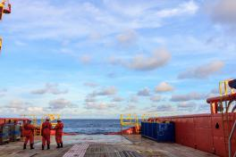 Seafarers standing on the deck of a vessel